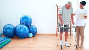 Smiling physiotherapist helping patient walk with zimmer frame