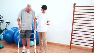 Smiling physiotherapist helping patient walk with walking frame