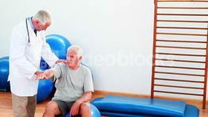 Smiling doctor helping patient move his arm and shoulder