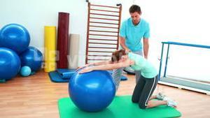 Trainer helping his client stretch her back with exercise ball