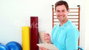 Smiling physical therapist writing on clipboard