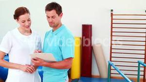 Smiling physical therapists looking at clipboard