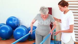 Physical therapist helping patient walk with parallel bars
