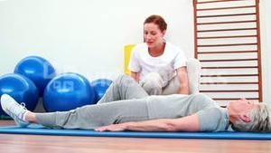 Physical therapist helping patient move her leg