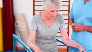 Physical therapist watching patient walk with parallel bars