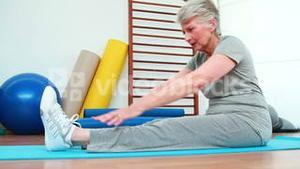 Elderly woman touching her toes on exercise mat