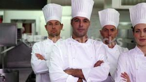 Four serious chefs looking at camera with arms crossed