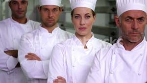Four stern chefs looking at camera with arms crossed