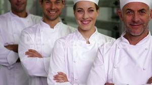 Four cheerful chefs looking at camera with arms crossed