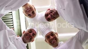 Team of chefs standing in circle looking down at camera