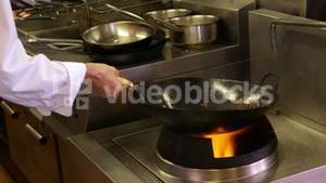 Chef tossing vegetables over a large flame