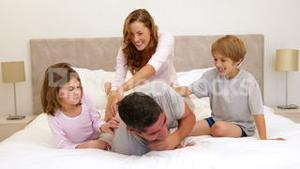 Cute parents and children lying on bed messing around