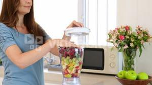 Smiling woman making a smoothie