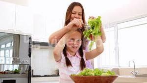 Mother showing her daughter how to toss a salad