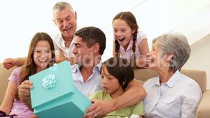 Extended family watching father open his present