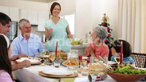 Mother bringing turkey to dinner table for christmas