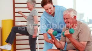 Senior citizens exercising with physiotherapist
