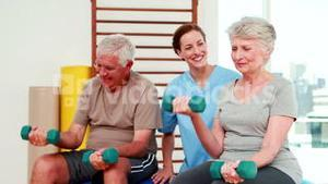 Happy senior citizens exercising with physiotherapist
