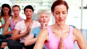 Group of peaceful women in fitness studio doing yoga