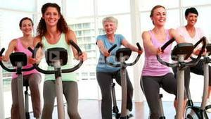 Group of smiling women in doing a spinning class