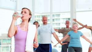 Pilates instructor smiling at camera in front of her class
