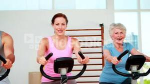 Happy diverse fitness group doing a spinning class