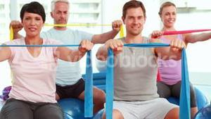 Group sitting on exercise balls stretching resistance bands