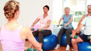 Fitness class sitting on exercise balls lifting hand weights