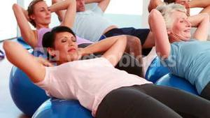Exercise class doing sit ups on exercise balls