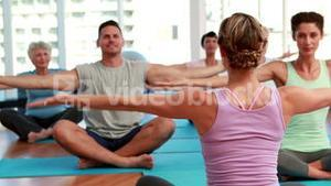 Yoga class sitting in lotus position together