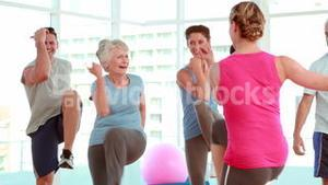 Aerobics class stepping and laughing together