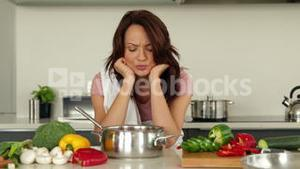 Puzzled woman looking down at her saucepan