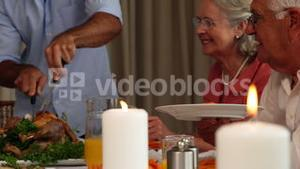 Father serving roast chicken at the dinner table