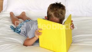 Little boy reading yellow book on bed