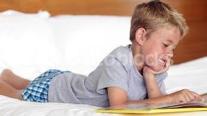 Little boy lying on bed reading a book