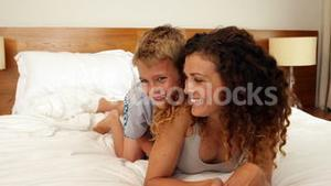 Son jumping on the bed to hug his mother