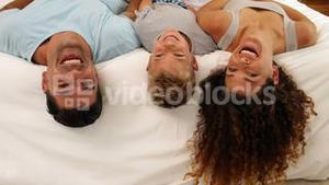 Family lying on bed posing for camera