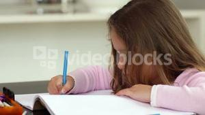 Little girl drawing at the kitchen table