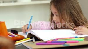 Little girl drawing at the kitchen table and smiling at camera