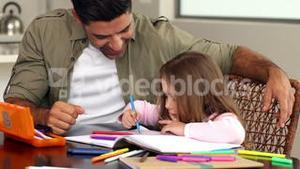 Little girl drawing at the table with her father