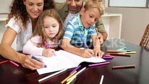 Cute children drawing at the table with their parents
