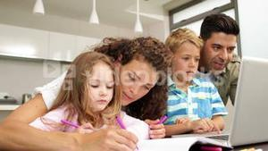 Cute children drawing at the table with their parents and using laptop