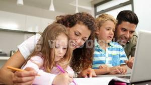 Happy children drawing at the table with their parents and using laptop