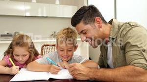 Children drawing with their dad at the table
