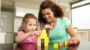 Mother and daughter playing with building blocks at the table