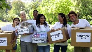 Group of young volunteers holding donation boxes