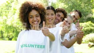 Volunteers standing in a row giving smiling at camera