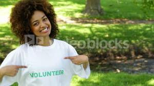 Pretty volunteer smiling at the camera and pointing to tshirt