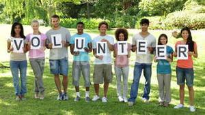 Group of casual young friends smiling at camera holding letters spelling volunteer