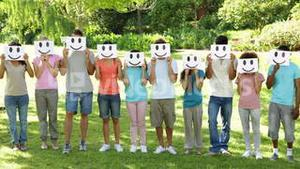 Group of casual young friends holding smiley faces over their faces